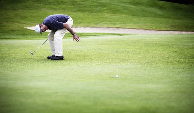 Golf player convulsed with laughter after ball just missed hole.