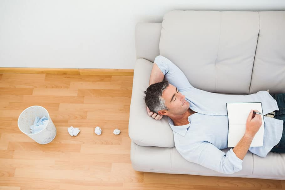 Man resting on couch with writer block at apartment